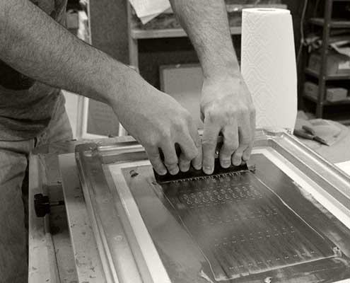 Solder paste being applied through silk screen onto LED light engine